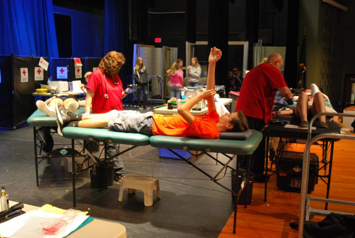 Michael+Newman+has+his+arm+in+the+air+awaiting+the+final+steps+of+the+blood+donation+process.