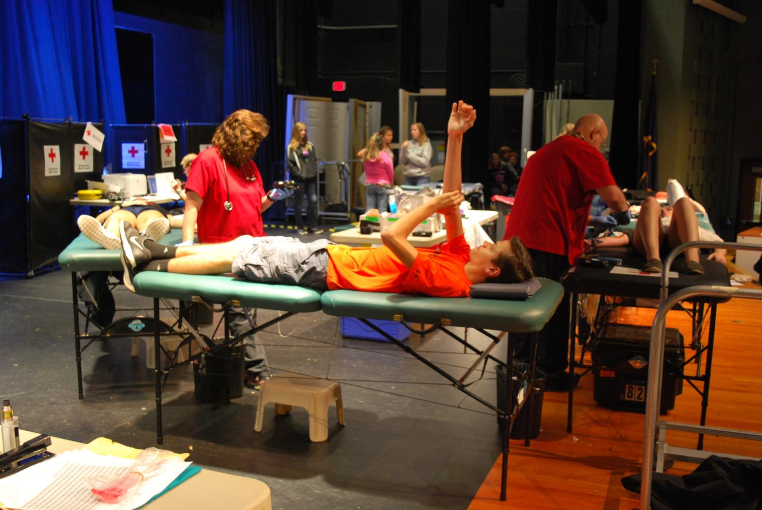 Michael Newman has his arm in the air awaiting the final steps of the blood donation process.