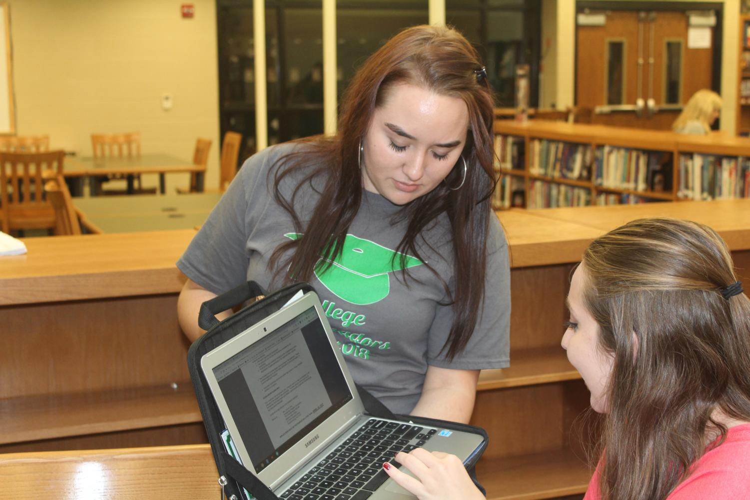 While lending a helping hand, Amber Brindle (12) chats with Maddie Hissong (12) to make the process more enjoyable.