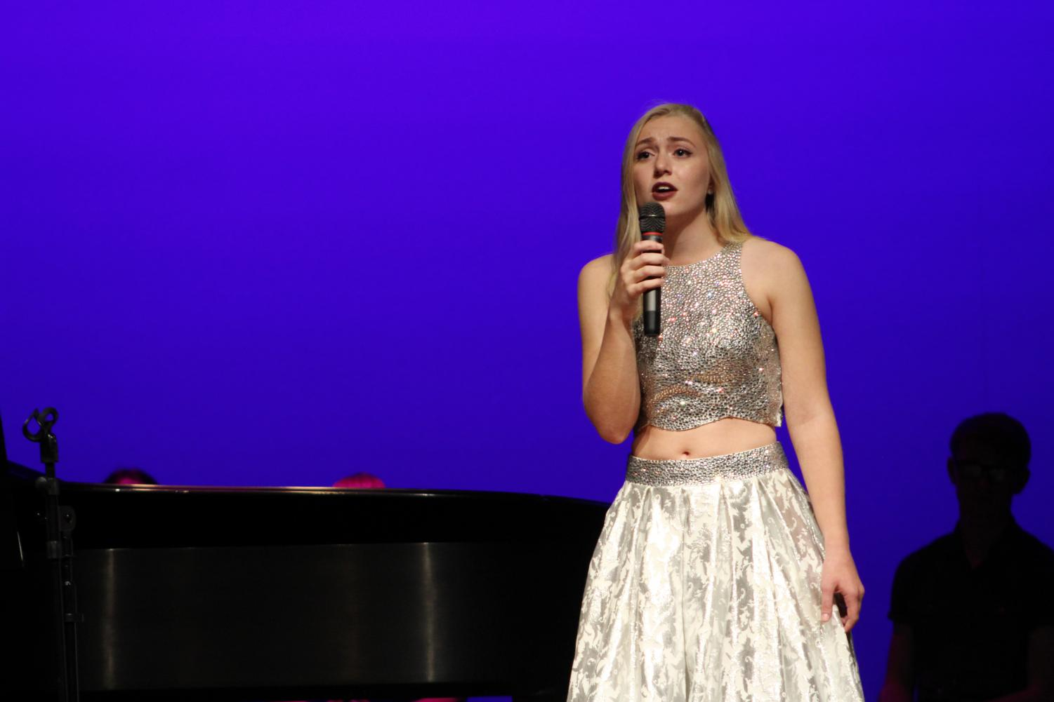 "Her dress sparkling under the stage lights, Olivia Harmon (11) performs ""Stars"" from Les Miserables."