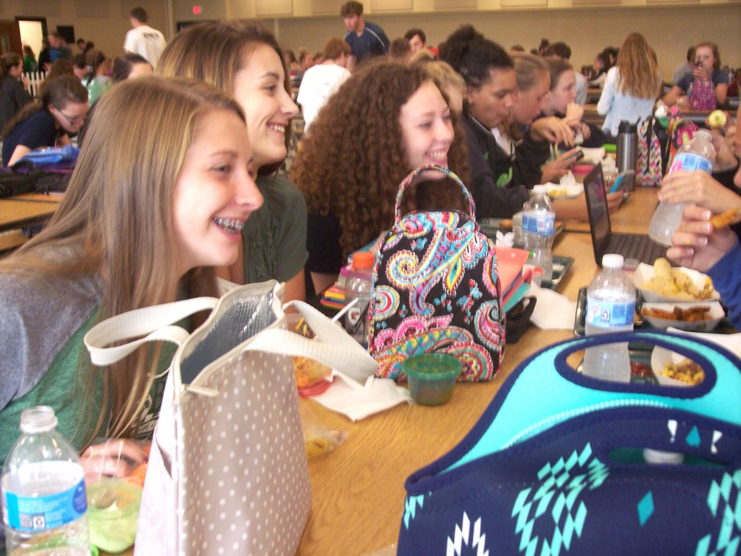Ashley Dukehart (9), Julia Trei (9), and Brynn Taulton (9) smile as they share a funny moment with their friends.