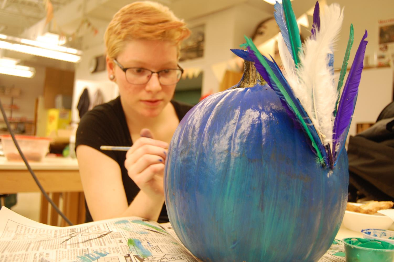 To add to the peacock on her pumpkin, Trinity Myers (12) adds feathers to emphasize the birds most noticeable trait.