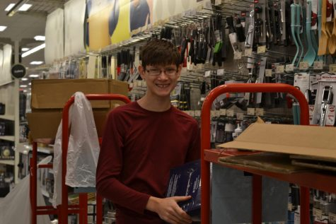 Edward Leevy (10) smiling for a picture while unloading boxes