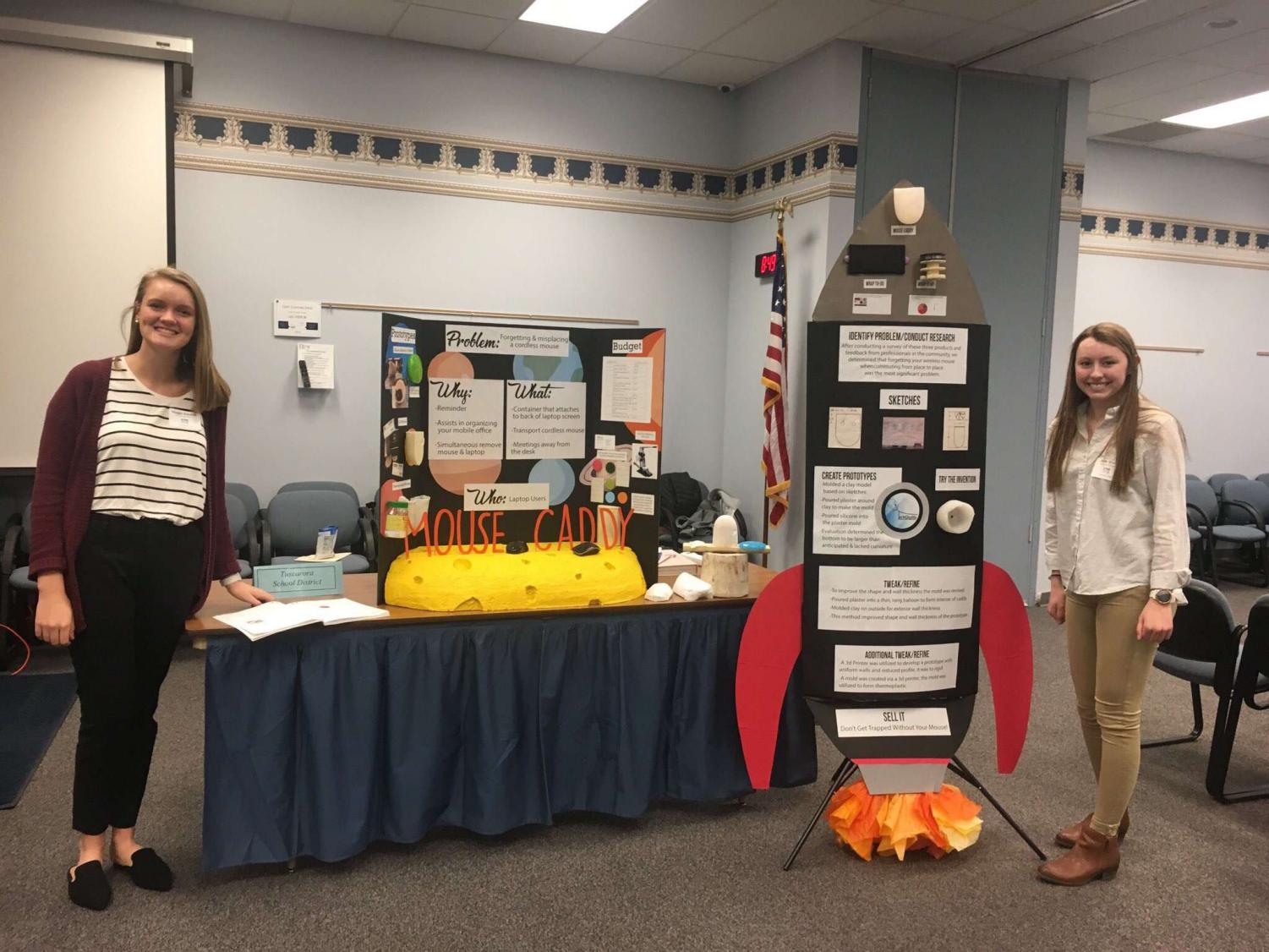 Maggie Strawoet (12) and Jade Wolfe (11) stand by their table presenting their invention at one of the competitions.
