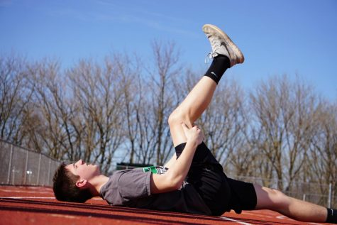 Owen Cooper (10) stretches out before track practice.
