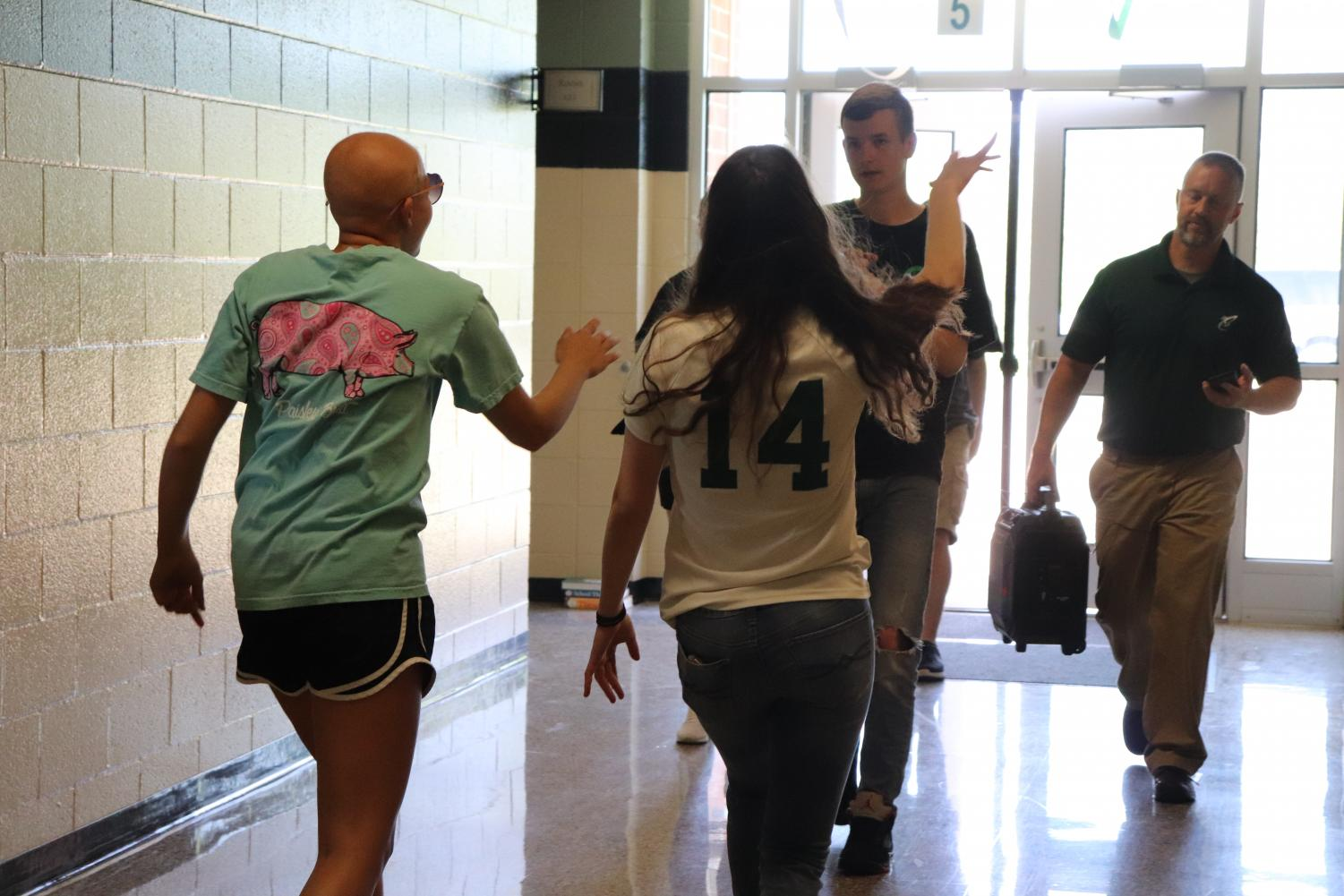 Cass Martin (12) and Hannah Kimmel (11) lip sync their portion of the Lip Dub project as Austin Thomas (10) films and Mr. Kevin Gustafson (Faculty) carries a speaker with the music.
