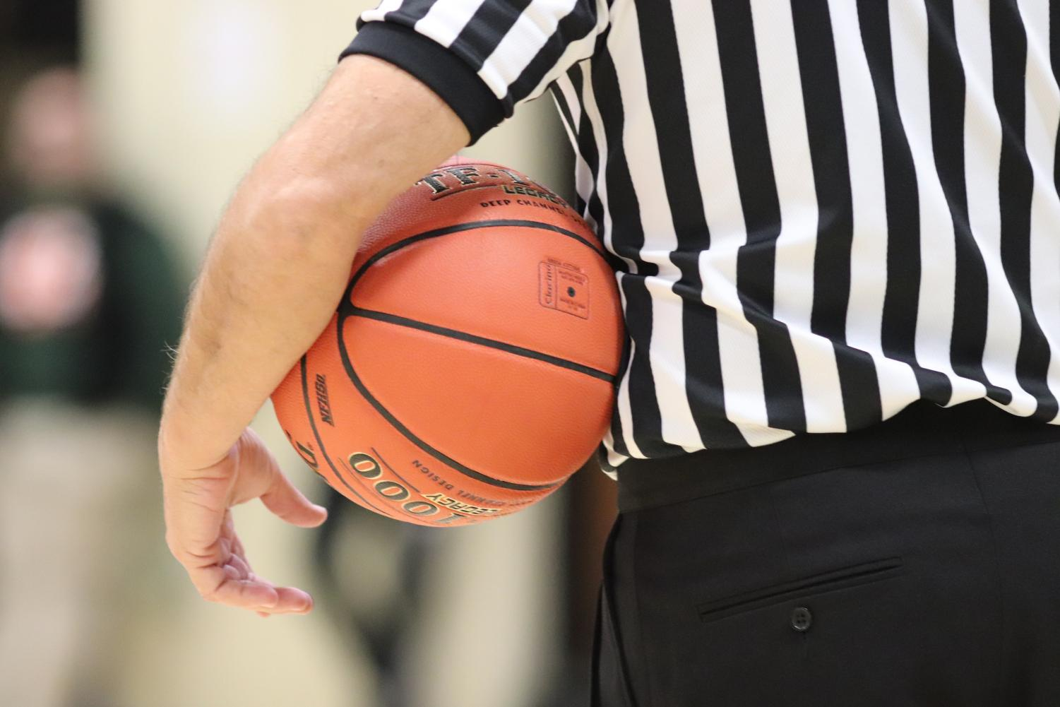 After traveling out of bounds, the ball rests in the referee's hands before being passed into play.
